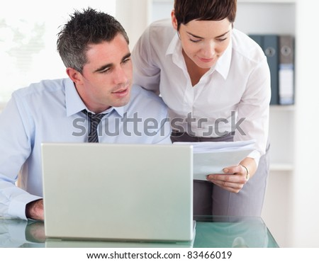 Colleagues comparing a blueprint folder to an electronic one in an office - stock photo