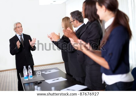 Colleagues congratulating a business man during a business meeting - stock photo