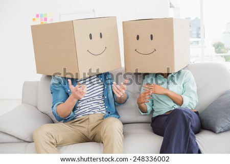 Colleagues covering their head with fun cardboard box in the office - stock photo