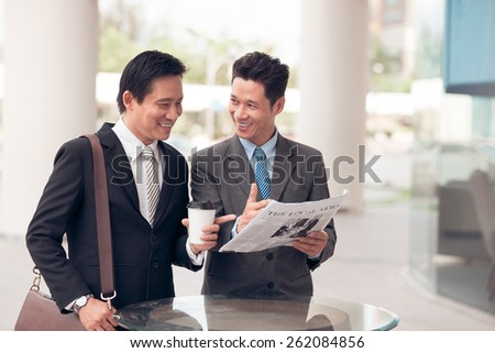Colleagues discussing newspaper outdoors