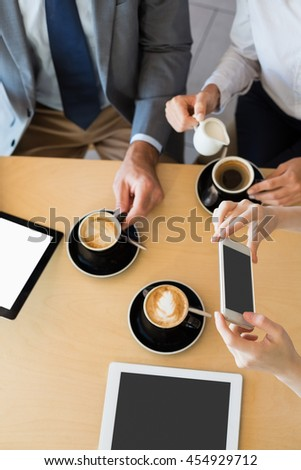 Colleagues having a cup of coffee while using mobile phone and digital tablet at restaurant