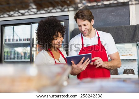 Colleagues in red apron using tablet at the bakery - stock photo
