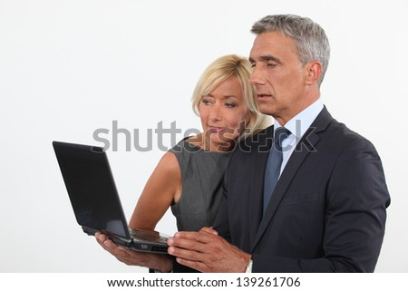 Colleagues looking at computer screen - stock photo