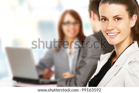 colleagues looking at laptop screen in office - stock photo