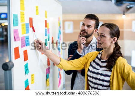 Colleagues looking at sticky notes on white board in the office