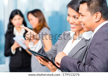 Colleagues looking at tablet together