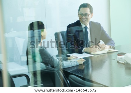 Colleagues Meeting in Conference Room, Shot Through Glass - stock photo
