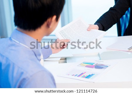 Colleagues passing a business document to each other - stock photo