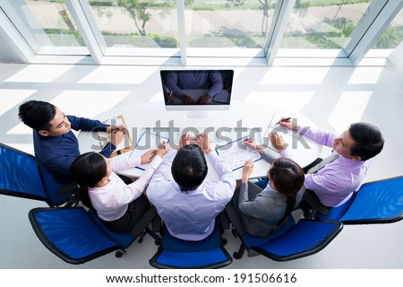 Colleagues sitting in front of the monitor in the office - stock photo