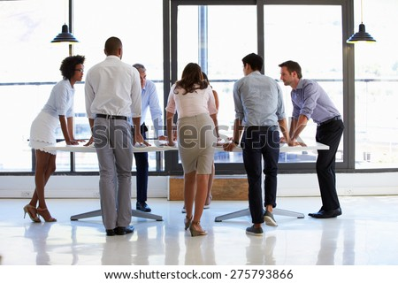 Colleagues standing around a conference table - stock photo