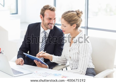 Colleagues using a digital tablet at desk in office - stock photo