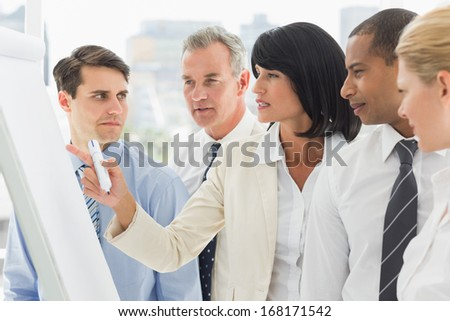 Colleagues watching businesswoman write on whiteboard in the office - stock photo