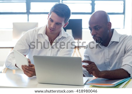 Colleagues working together at their desk in the office - stock photo