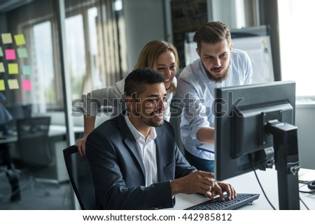 Colleagues working together on a computer. - stock photo