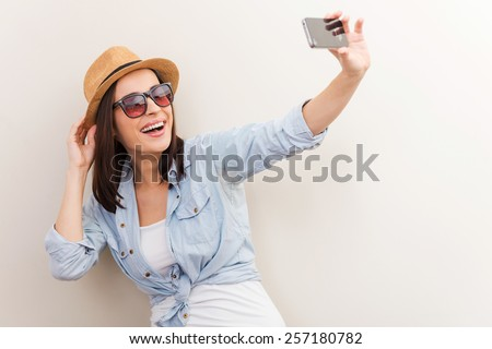 Collecting memories. Portrait of beautiful young woman in glasses adjusting her hat while making selfie and standing against brown background - stock photo