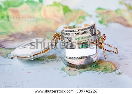 Collecting money for travel. Glass tin as moneybox with cash savings (banknotes and coins) on map as background. White empty space for your text. - stock photo