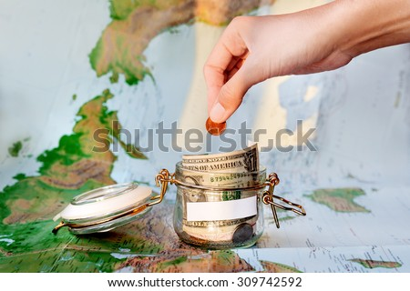 Collecting money for travel. Glass tin as moneybox with cash savings (banknotes and coins) on map as background in sunlight. White empty space for your text. Woman puts two euro cents coin in jar. - stock photo