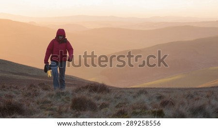 Collecting water for a wild campsite below the summit of the Cheviot in Northumberland. - stock photo
