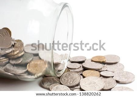 Collection of Australian coins spilling out of a glass jar tipped on its side - stock photo