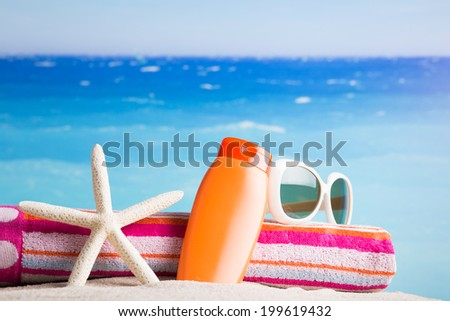 Collection of beach items - lotion, starfish, beautiful towel, sunglasses on the beach - stock photo