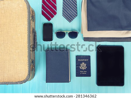 collection of business travel items with a vintage filter on a turquoise background - stock photo