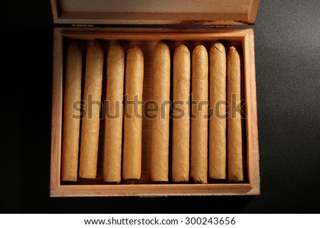 Collection of cigars in humidor on black table, top view - stock photo