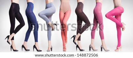 collection of colorful tights and stockings on sexy woman legs isolated on grey - stock photo