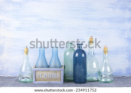 Collection of decorative bottles on blue wooden background.