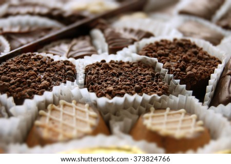 Collection of different chocolate candies on white packaging closeup. - stock photo
