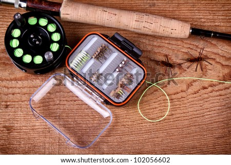 Collection of fly fishing equiptment on a wooden plank - stock photo