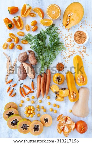 Collection of fresh orange toned vegetables and fruit raw produce on white rustic background, pumpkin butternut carrot papaya pawpaw capsicum pepper sweet potato cherry tomatoes chilli orange - stock photo
