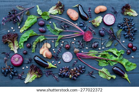 Collection of fresh purple fruit and vegetables on the black wooden table - stock photo