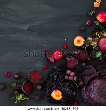 Collection of Fresh Purple Fruits and Vegetables such as Plums, Beetroots, Onions, Aubergine, Lettuce, Cabbage, Beans, Figs, Grapes on the Dark Background with Top View - stock photo