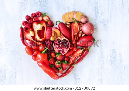 Collection of fresh red vegetables and fruits arranged in a heart shape on white rustic background strawberry raspberry pomegranate peppers capsicum chilli potato beans legumes overhead flat lay - stock photo