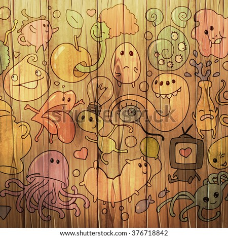 Collection of funny colorful cartoon doodle illustrations on a wooden surface - stock photo