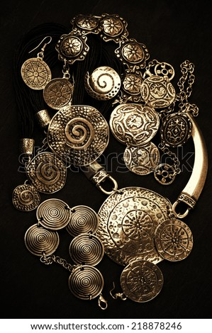 Collection of golden ethnic jewelry on black background. - stock photo
