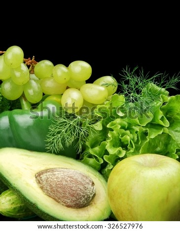 Collection of green vegetables and fruits-lettuce,bell pepper,dill leaves,cucumbers,grapes,apple and avocado on black background