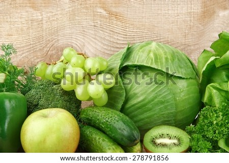 Collection of green vegetables and fruits on wooden background