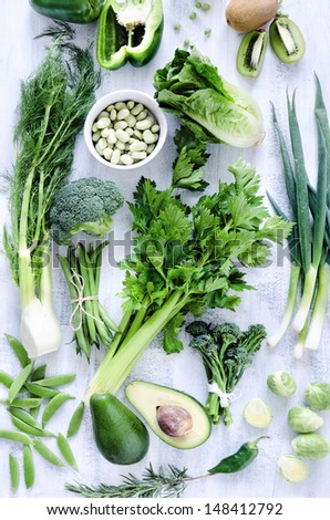 Collection of green vegetables on rustic white background from overhead, broccoli, celery, avocado, brussels sprouts, kiwi, pepper, peas, beans, lettuce, - stock photo