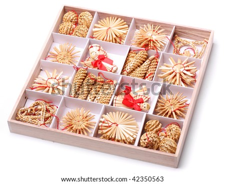 Collection of Handmade christmas decorations from straw, traditional Czech souvenirs in wooden box, isolated on white - stock photo