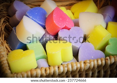 Collection of heart shaped soaps in wicker basket . - stock photo