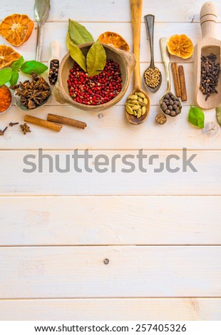 Collection of herbs and spices on a wooden background with space for text - stock photo