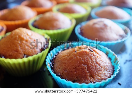 Collection of home made muffins on colorful silicon forms - stock photo