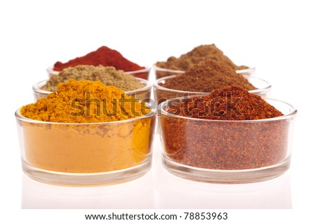 collection of indian spices (cumin, coriander, paprika, garam masala, turmeric, chili powder) on glass cups isolated on white background - stock photo