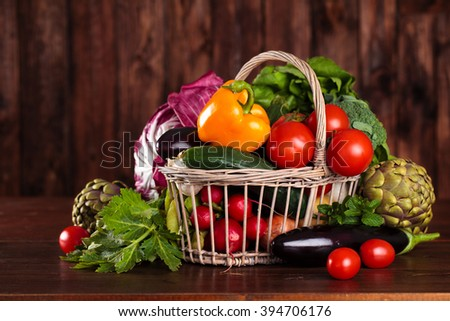 Collection of mixed organic vegetables and herbs in basket. In rustic background. - stock photo
