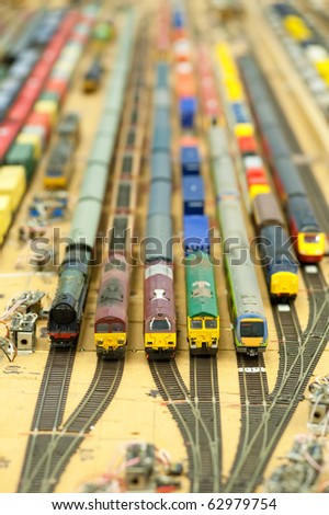 collection of model trains in an unfinished miniature goods yard - stock photo