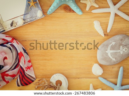 collection of nautical and beach objects creating a frame over wooden background,  - stock photo