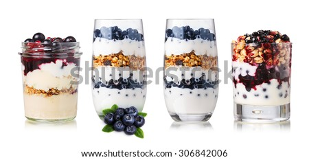 Collection of parfait desserts or snacks in glasses and jars. American parfait with muesli,granola,yogurt,puffed wheat,fresh berries and jam - stock photo
