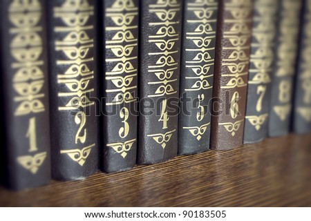 Collection of several volumes of books on a wooden shelf - stock photo