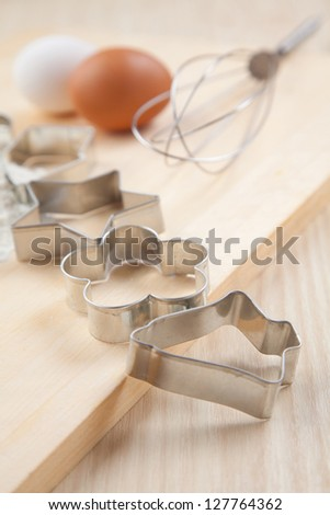collection of silver  Cookie cutter forms with flour on wooden board